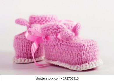 Knitted baby booties on a background