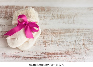 knitted baby socks with rose bow on the wooden surface