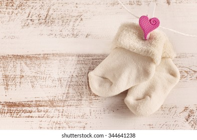 knitted baby socks with rose heart on the wooden surface