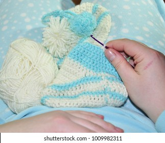 knitted baby socks of white and blue acrylic yarn. handmade clothes. on a blue background is a ball of yarn and related products. lesson crochet, air loop, column, openwork pattern.