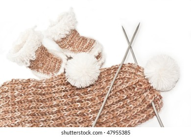 Knitted baby's bootees and a white scarf, brown for babies, toddlers