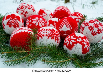 Knitted balls with ornament for new year and christmas decoration on spruce branch