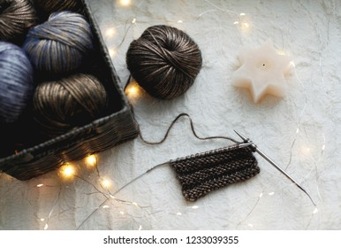 knitted basket with yarn, needles and candle