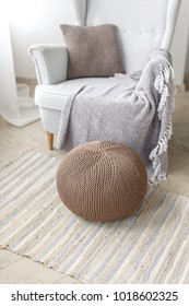 a knitted beige pouf in a modern interior, a stylish pouf on the background of an armchair and a plaid, a Scandinavian style in the interior