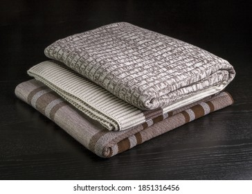 Knitted blanket folded on a dark background.