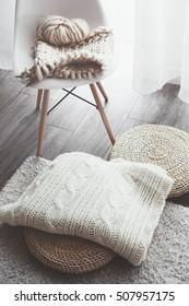 Knitted blanket on wicker ottoman, modern plastic chair in living room. Details of white scandinavian interior.