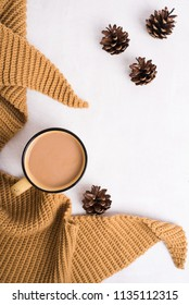 Knitted camel shawl, cup of coffee and cones on white background