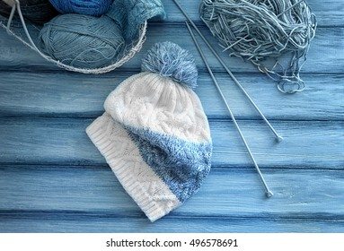 Knitted cap with yarn, needles and metal basket on wooden background