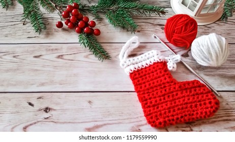 Knitted Christmas stocking and wool yarn balls on wooden background