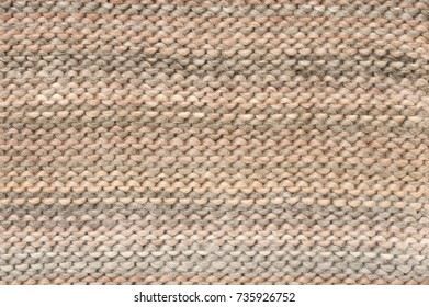 Knitted cloth purl stitch texture of melange beige and brown colored woolen yarn.