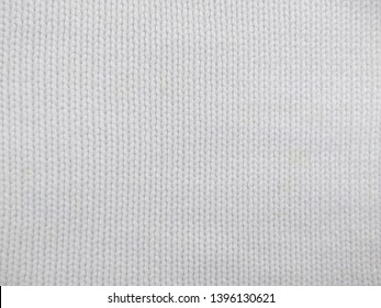 Knitted clothes from wool yarn. Background of wool yarn for yarn frame. White knitting yarn for handicrafts background.
