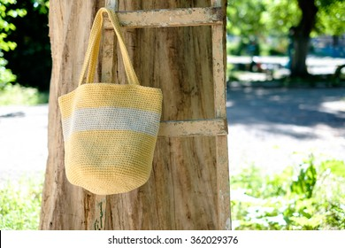 knitted crochet bag of yellow color on the background of nature