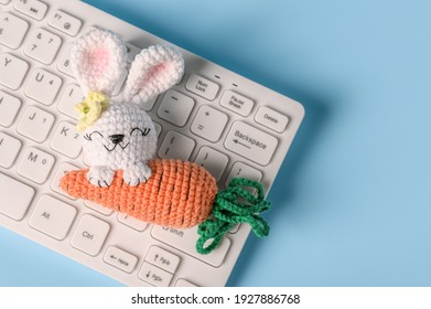 Knitted Easter bunny on a blue background with a keyboard. Happy easter. Blank for Easter greetings for people whose profession is connected with a computer.