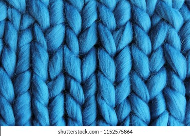 Knitted fabric of bulk yarn of blue color. Natural wool. Knitting with hands.