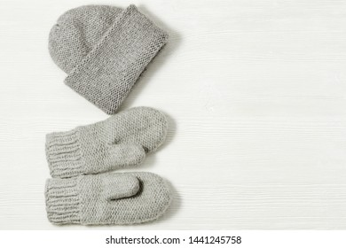 Knitted grey mittens and hat on white wood background. Warm clothing. Top view. Copy space.