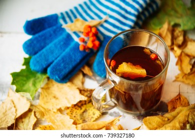 knitted hat and gloves with autumn leaves and a thermos of tea, the concept of the background on the subject of coziness, comfort, warmth