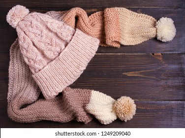 Knitted hat and scarf, winter concept. Women winter warm accessories on wooden background. Flat lay, view from above, top