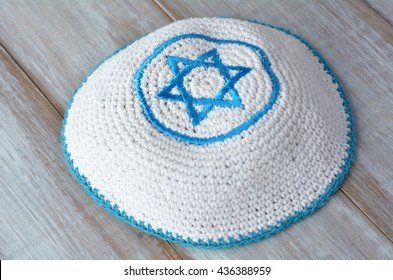 Knitted kippah with embroidered blue and white Star of David on a wooden table. Jewish lifestyle concept copy space