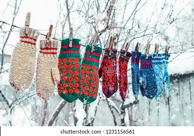 knitted mittens on winter background. mittens under falling snow. Winter season symbol. Christmas and new year season