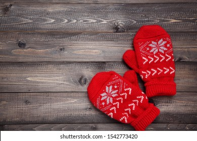 Knitted mittens on wooden table