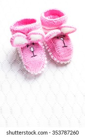 Knitted pink baby booties with rabbit muzzle over textile background
