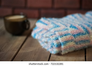 The knitted plaid of a multi-colored wool. Handmade. Heat of the home. Plaid and a cup of coffee or cocoa