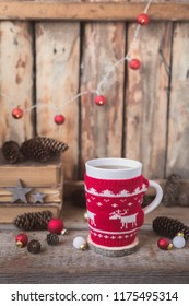 Knitted red cup with white reindeer, christmas lights with old books, cones and toys at background, postcard concept