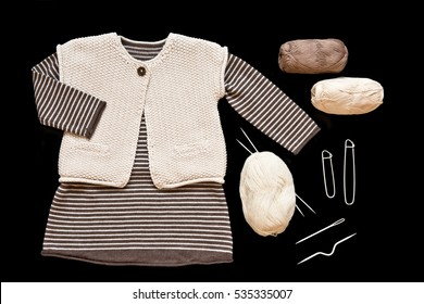 Knitted set (dress and west) for the baby girl with balls of wool and knitting needles isolated on black background/ Knitting / Hobby