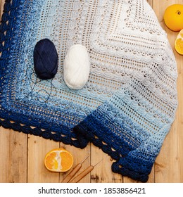 Knitted shawl, balls of thread and oranges on wooden background