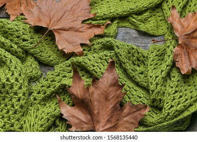 Knitted shawl with leaves on an old wooden table