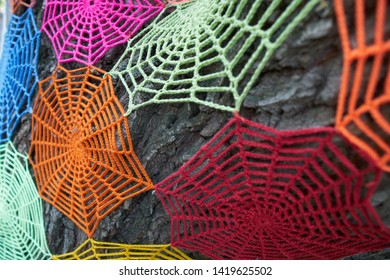 Knitted spider web on a tree.