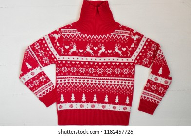 Knitted sweater with red with white pattern on wooden white background. ugly sweater