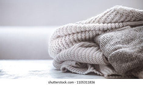 knitted sweaters on a wooden background, space for text