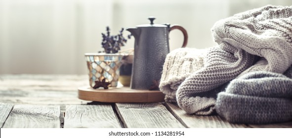 Knitted sweaters on a wooden background in the interior of the living room, space for text