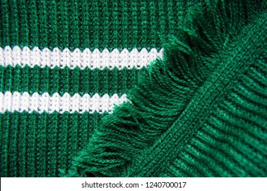 Knitted texture of green warm scarf with white stripes and fringe. Slytherin scarf, knitted background