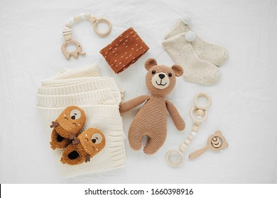 Knitted toy bear, blanket, socks,  and wooden teether for newborn on white bed.  Gender neutral  baby stuff and accessories. Flat lay, top view