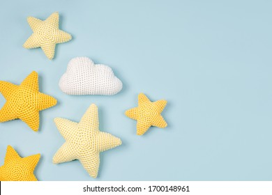 Knitted toy  yellow stars on blue  background. Baby stuff and accessories. Flat lay, top view