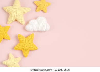 Knitted toy  yellow stars on pink background. Baby stuff and accessories. Flat lay, top view