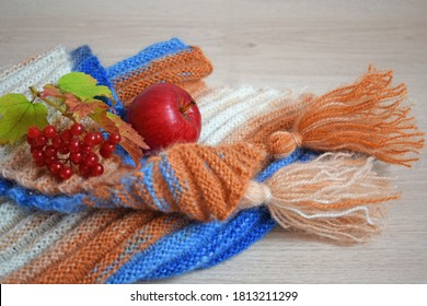 Knitted triangular scarf and fruit on a gray background.