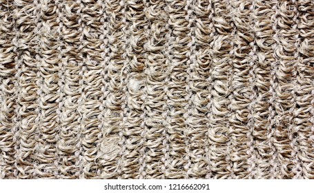 Knitted washcloth texture. Pattern of coarse knit beige fabric. Light brown background, close up.