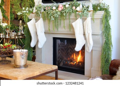 Knitted white Christmas stockings hanging on a fireplace mantle.