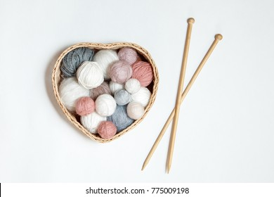knitted white hat with tangles in a basket and wooden knitting needles on a white background