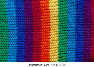 A knitted wool fabric in the colors of the rainbow. Fun background. Vertical strip