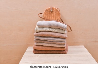 Knitted wool sweaters. Bamboo round handbag on Pile of knitted winter clothes on wooden background