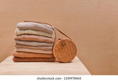 Knitted wool sweaters. Pile of knitted winter clothes with round bamboo handbag on wooden background
