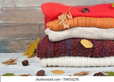 Knitted wool sweaters. Pile of knitted winter, autumn clothes on wooden background, sweaters, knitwear, leaf space for text