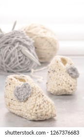 Knitting baby booties and wool yarns on soft background. Hand-made socks for the baby