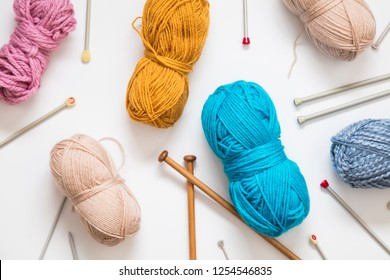 Knitting background. Balls of wool and knitting needles on a plain background