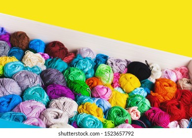 Сrocheting and knitting. Colorful multicolored skeins of yarn in the box on a yellow background. Women's hobby.