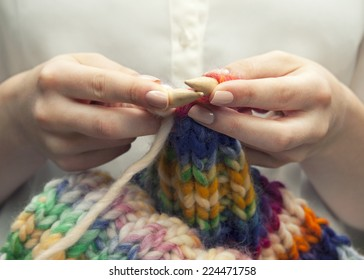 Knitting a colorful scarf, closeup of the hands